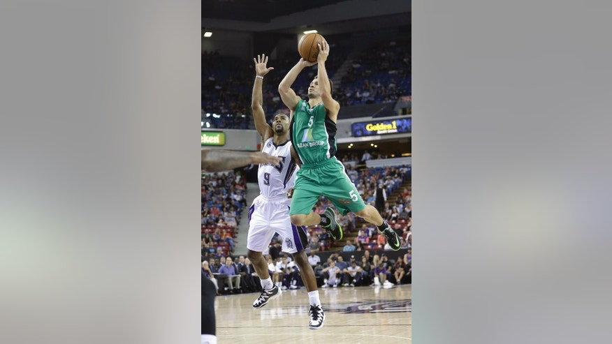 Maccabi Haifa guard Brody Angley, right, shoots against Sacramento Kings guard Ramon Sessions during the first quarter of an NBA exhibition game in Sacramento, Calif., Saturday, Oct. 18, 2014. (AP Photo/Rich Pedroncelli)