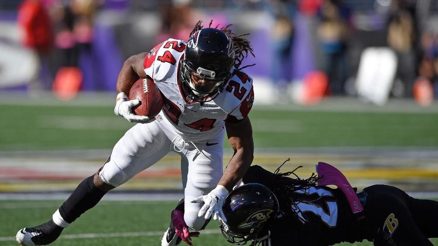 Atlanta Falcons running back Devonta Freeman (24) is tackled by Baltimore Ravens cornerback Lardarius Webb in the second half of an NFL football game, Sunday, Oct. 19, 2014, in Baltimore. (AP Photo/Nick Wass)