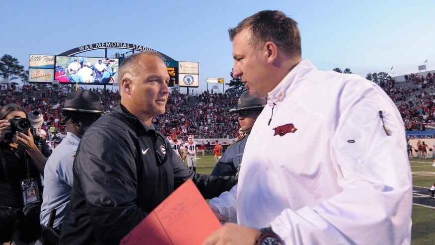 Georgia coach Mark Richt, left, greets Arkansas coach Bret Bielema after Georgia's 45-32 victory in an NCAA college football game in Little Rock, Ark., Saturday, Oct. 18, 2014. (AP Photo/David Quinn)