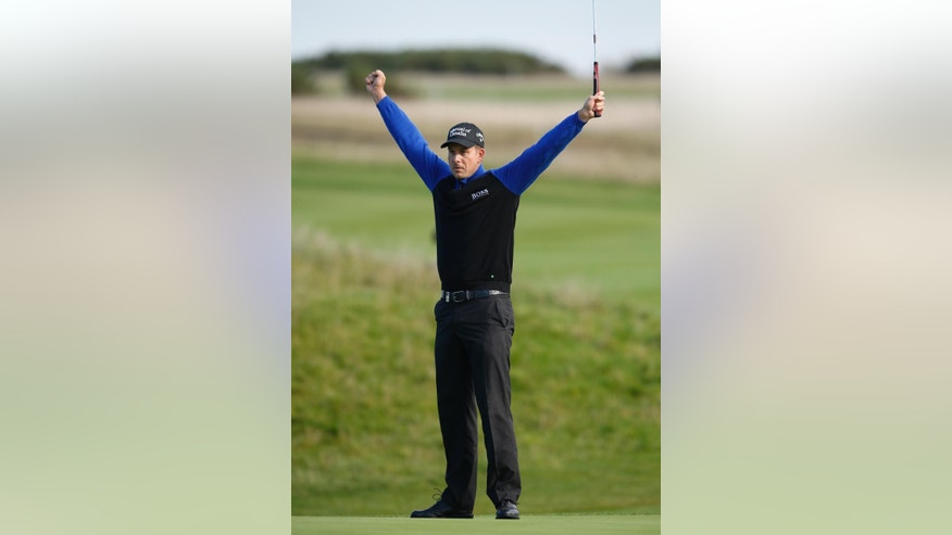 Henrik Stenson of Sweden celebrates after putting out on the 18th green to win his semifinal World Match Play Championship game against George Coetzee of South Africa at the Royal London golf club in Ash, England Sunday Oct. 19, 2014. Stenson won the semifinal and will play Mikko Ilonen of Finland in the final. (AP Photo/Alastair Grant)