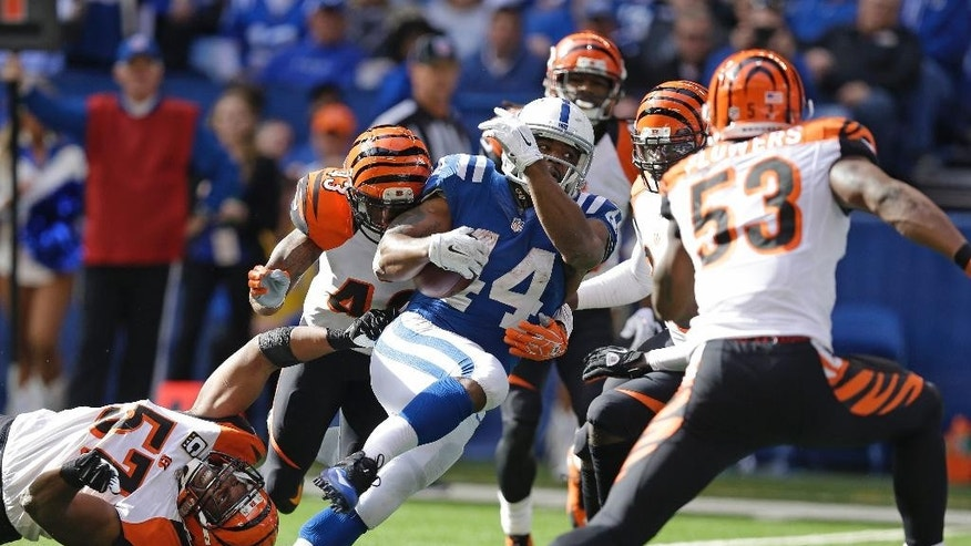 Indianapolis Colts running back Ahmad Bradshaw dives into the end zone for a 10-yard touchdown reception against Cincinnati Bengals outside linebacker Vincent Rey (57) and George Iloka (43) during the second half of an NFL football game Sunday, Oct. 19, 2014, in Indianapolis. (AP Photo/Michael Conroy)