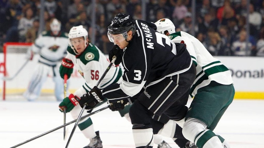 Los Angeles Kings'  Brayden McNabb (3) chases the puck as Minnesota Wild left wing Erik Haula (56) defends in the first period of an NHL hockey game in Los Angeles on Sunday, Oct. 19, 2014. (AP Photo/Christine Cotter)
