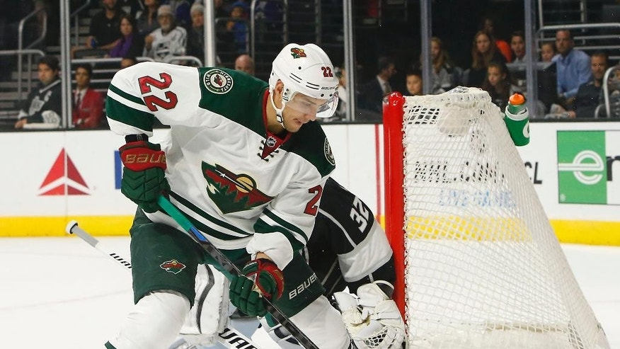 Minnesota Wild right wing Nino Niederreiter (22) controls the puck in front of the Los Angeles Kings goalie Jonathan Quick in the first period of an NHL hockey game in Los Angeles on Sunday, Oct. 19, 2014. (AP Photo/Christine Cotter)