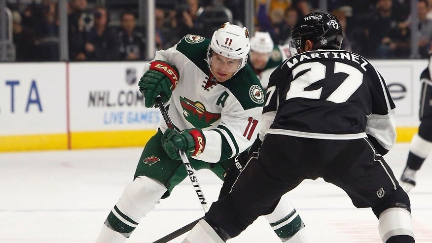 Minnesota Wild left wing Zach Parise (11) passes the puck past Los Angeles Kings defenseman Alec Martinez (27) in the first period of an NHL hockey game in Los Angeles, Sunday, Oct. 19, 2014. (AP Photo/Christine Cotter)