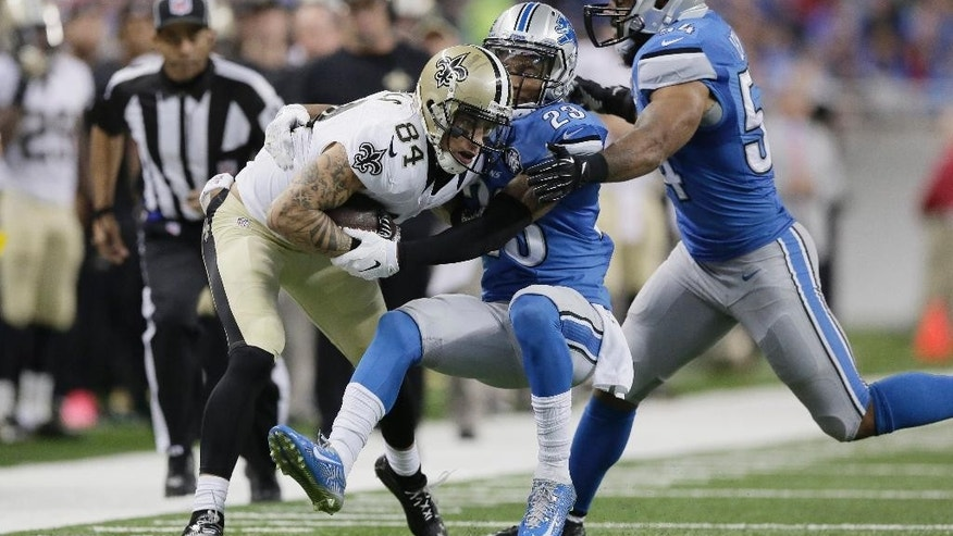 New Orleans Saints wide receiver Kenny Stills (84) is tackled by Detroit Lions cornerback Darius Slay (23) and outside linebacker DeAndre Levy (54) during the second half of an NFL football game in Detroit, Sunday, Oct. 19, 2014. (AP Photo/Duane Burleson)
