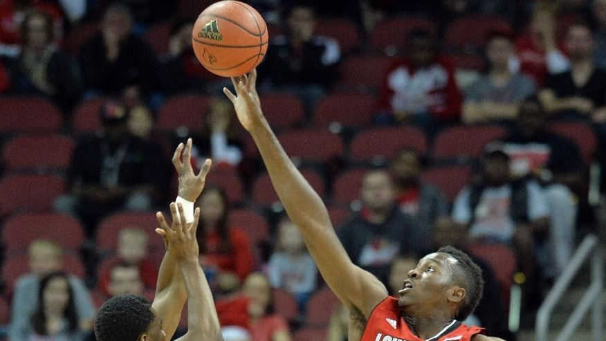 Louisville's Chinanu Onuaku, right, blocks the shot of Louisville's Anton Gill during the first half of an NCAA college basketball scrimmage Sunday, Oct. 19, 2014, in Louisville, Ky. (AP Photo/Timothy D. Easley)