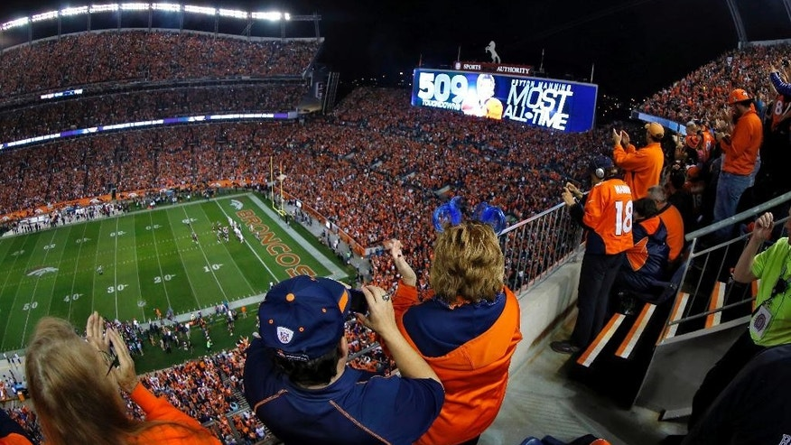 Denver Broncos fans cheer after Peyton Manning threw his 509th career touchdown pass during the first half of an NFL football game against the San Francisco 49ers, Sunday, Oct. 19, 2014, in Denver. (AP Photo/David Zalubowski)