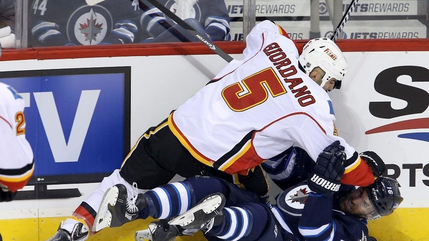 Calgary Flames' Mark Giordano (5) gets tangled with Winnipeg Jets' Andrew Ladd (16) during first period NHL hockey action in Winnipeg, Manitoba, Sunday, Oct. 19, 2014. (AP Photo/The Canadian Press, Trevor Hagan)