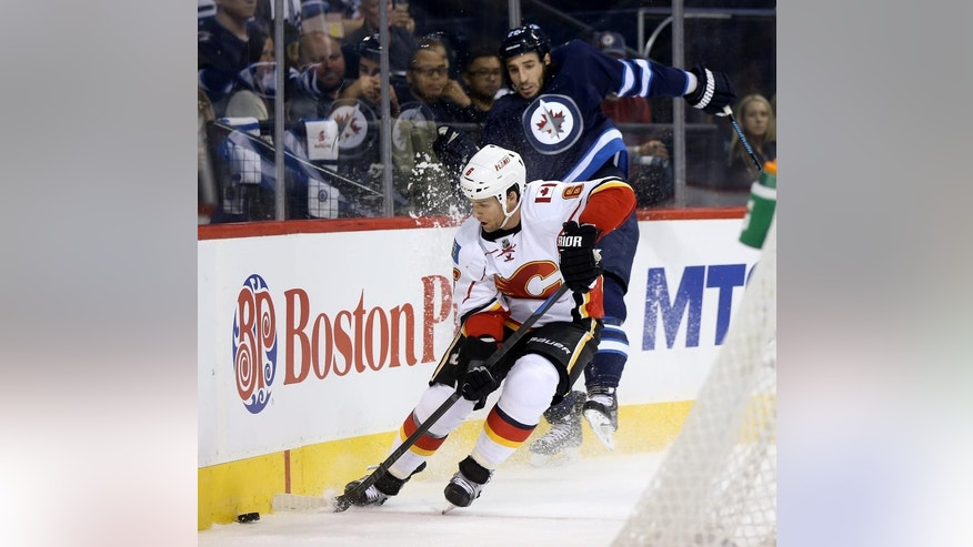 Calgary Flames' Dennis Wideman (6) beats Winnipeg Jets' Chris Thorburn (22) to the puck during second period NHL hockey action in Winnipeg, Manitoba, Sunday, Oct. 19, 2014. (AP Photo/The Canadian Press, Trevor Hagan)