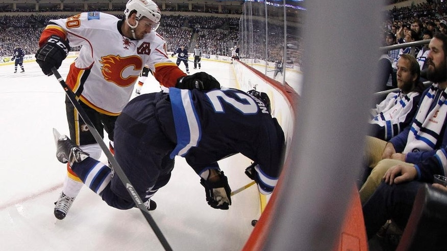 Calgary Flames' Curtis Glencross (20) shoves Winnipeg Jets' Chris Thorburn (22) into the boards during second period NHL hockey action in Winnipeg, Manitoba, Sunday, Oct. 19, 2014. (AP Photo/The Canadian Press, Trevor Hagan)