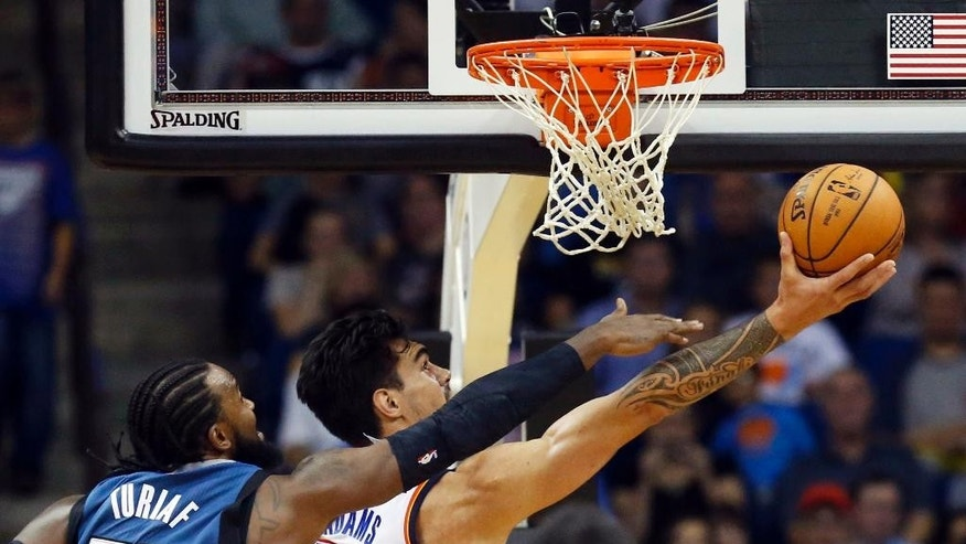 Oklahoma City Thunder center Steven Adams (12) shoots in front of Minnesota Timberwolves center Ronny Turiaf (32) in the third quarter of an NBA preseason basketball game in Tulsa, Okla., Sunday, Oct. 19, 2014. Minnesota won 112-94. (AP Photo/Sue Ogrocki)