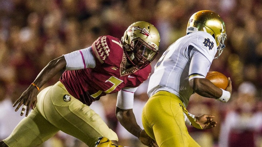 Florida State linebacker Matthew Thomas, left, chases down Notre Dame quarterback Everett Golson in the first half of an NCAA college football game in Tallahassee, Fla., Saturday, Oct. 18, 2014. (AP Photo/Mark Wallheiser)