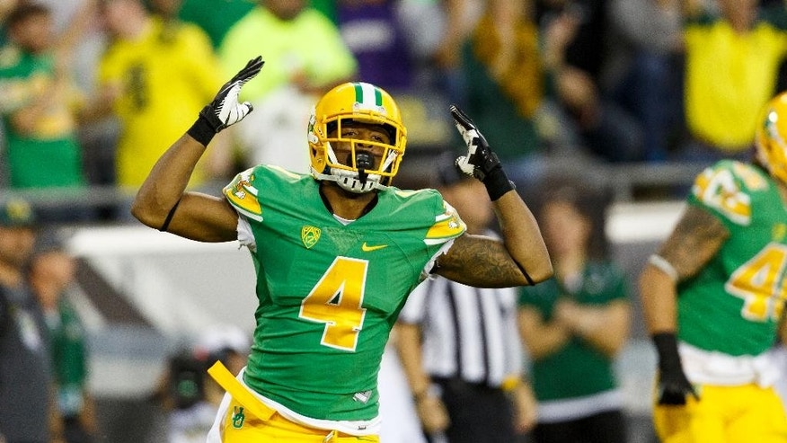 Oregon defensive back Erick Dargan (4) celebrates after making an interception during the second quarter against Washington in an NCAA college football game in Eugene, Ore., Saturday, Oct. 18, 2014. (AP Photo/Ryan Kang)