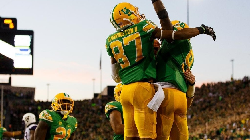 Oregon wide receiver Darren Carrington (87) and Oregon running back Byron Marshall (9) jump in the air after an Oregon touchdown during the second quarter against Washington in an NCAA college football game in Eugene, Ore., Saturday, Oct. 18, 2014. (AP Photo/Ryan Kang)