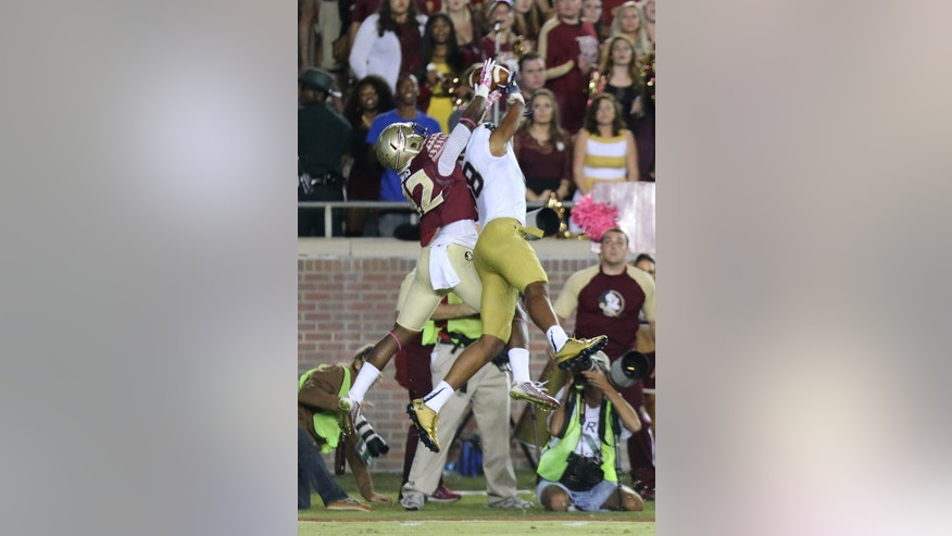 Notre Dame's Corey Robinson and Florida State's Jarred Higgins go up for a pass in the third quarter of an NCAA college football game, Saturday, Oct. 18, 2014 in Tallahassee, Fla. The pass was incomplete. Florida State won 31-27. (AP Photo/Steve Cannon)