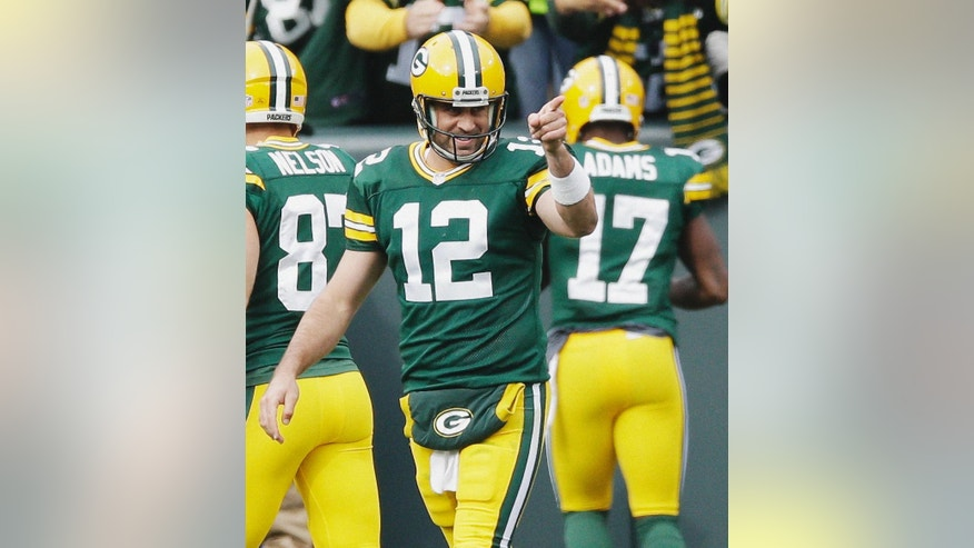 Green Bay Packers quarterback Aaron Rodgers celebrates a touchdown pass to Davante Adams (17) during the second half of an NFL football game against the Carolina Panthers Sunday, Oct. 19, 2014, in Green Bay, Wis. (AP Photo/Tom Lynn)