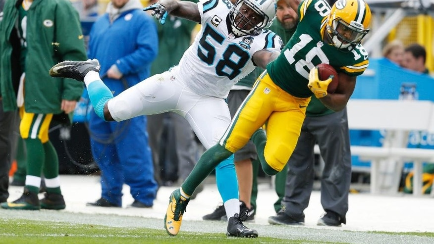 Green Bay Packers' Randall Cobb catches a pass in front of Carolina Panthers' Thomas Davis (58) during the second half of an NFL football game Sunday, Oct. 19, 2014, in Green Bay, Wis. (AP Photo/Mike Roemer)