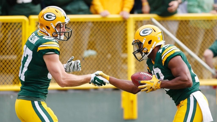 Green Bay Packers' Jordy Nelson (87) is congratulated by teammate Randall Cobb after Nelson's touchdown catch during the first half of an NFL football game against the Carolina Panthers Sunday, Oct. 19, 2014, in Green Bay, Wis. (AP Photo/Mike Roemer)
