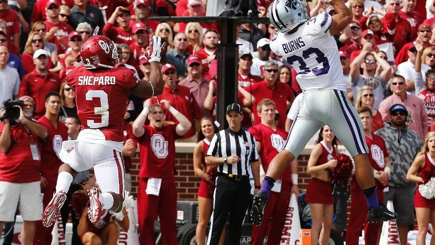 Kansas State defensive back Morgan Burns (33) intercepts a pass intended for Oklahoma wide receiver Sterling Shepard (3) in the third quarter of an NCAA college football game in Norman, Okla., Saturday, Oct. 18, 2014. Kansas State won 31-30. (AP Photo/Sue Ogrocki)