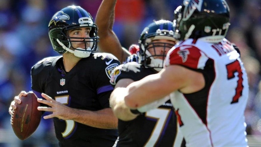 Baltimore Ravens quarterback Joe Flacco, left, looks for a receiver as he is pressured in the first half of an NFL football game against the Atlanta Falcons, Sunday, Oct. 19, 2014, in Baltimore. (AP Photo/Gail Burton)