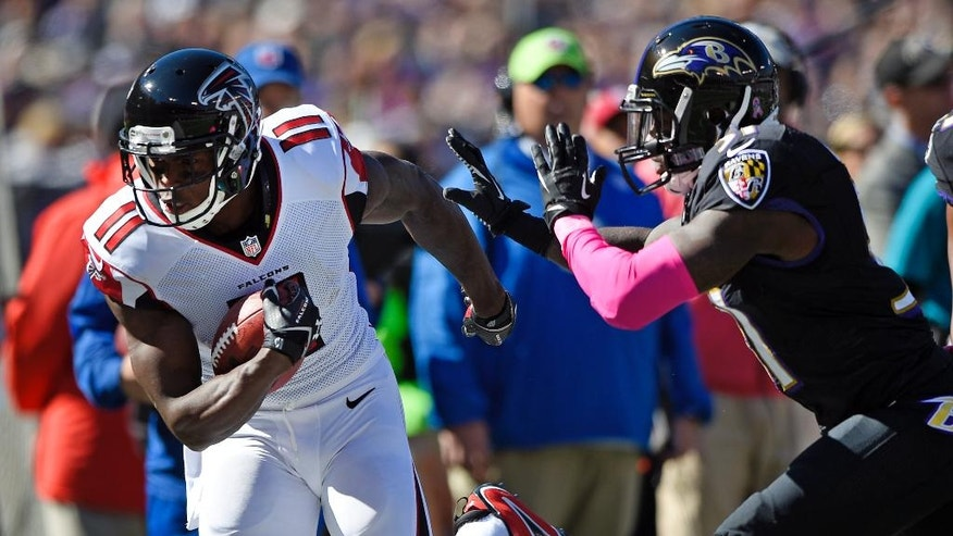 Atlanta Falcons wide receiver Julio Jones, left, rushes out of bounds in front of Baltimore Ravens free safety Terrence Brooks in the first half of an NFL football game, Sunday, Oct. 19, 2014, in Baltimore. (AP Photo/Nick Wass)