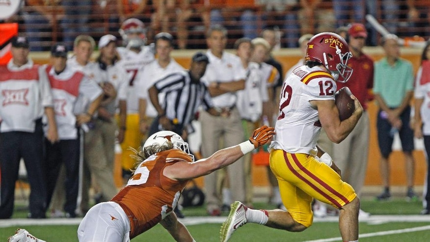 Iowa State quarterback Sam Richardson (12) runs the ball against Texas linebacker Dalton Santos (55) during the first quarter of an NCAA college football game in Austin, Texas, Saturday, Oct. 18, 2014. (AP Photo/Michael Thomas)