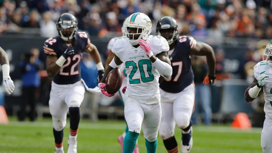 Miami Dolphins safety Reshad Jones (20) runs with the ball after intercepting a pass against the Chicago Bears during the first half of an NFL football game Sunday, Oct. 19, 2014 in Chicago. (AP Photo/Nam Y. Huh)