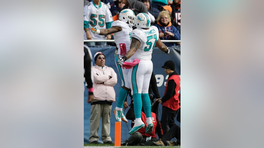 Miami Dolphins wide receiver Mike Wallace (11) celebrates his touchdown reception with center Mike Pouncey (51) during the first half of an NFL football game against the Chicago Bears Sunday, Oct. 19, 2014 in Chicago. (AP Photo/Nam Y. Huh)