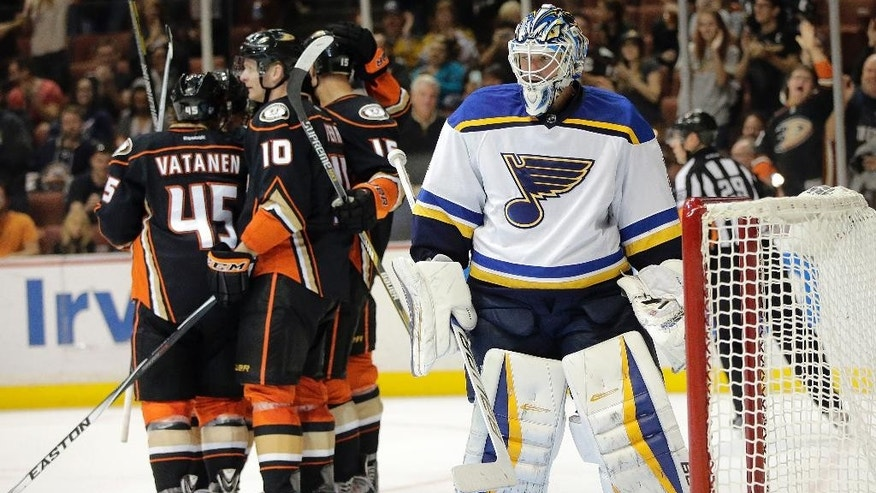 St. Louis Blues goalie Brian Elliott stands on the ice as the Anaheim Ducks players celebrate a goal by Sami Vatanen(45), of Finland, during the second period of an NHL hockey game Sunday, Oct. 19, 2014, in Anaheim, Calif. (AP Photo/Jae C. Hong)