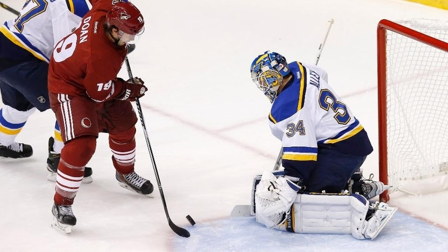 St. Louis Blues' Jake Allen (34) makes a save on a shot by Arizona Coyotes' Shane Doan (19) as Blues' Alex Pietrangelo, left, defends during the first period of an NHL hockey game Saturday, Oct. 18, 2014, in Glendale, Ariz. (AP Photo/Ross D. Franklin)