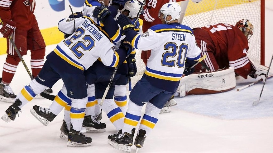St. Louis Blues' Kevin Shattenkirk (22), Alexander Steen (20) and Jaden Schwartz celebrate a goal scored by St. Louis Blues' David Backes, second from left, as Arizona Coyotes' Mike Smith, right, tries to get up off the ice during the first period of an NHL hockey game Saturday, Oct. 18, 2014, in Glendale, Ariz. (AP Photo/Ross D. Franklin)