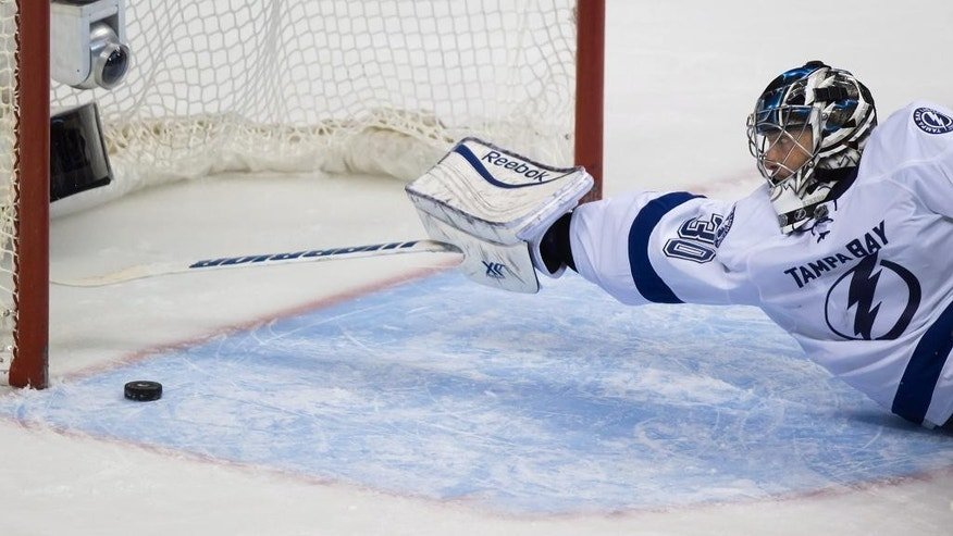 Tampa Bay Lightning goalie Ben Bishop reaches back to keep the puck from entering the goal during the third period of an NHL hockey game against the Vancouver Canucks on Saturday, Oct. 18, 2014, in Vancouver, British Columbia. (AP Photo/The Canadian Press, Darryl Dyck)