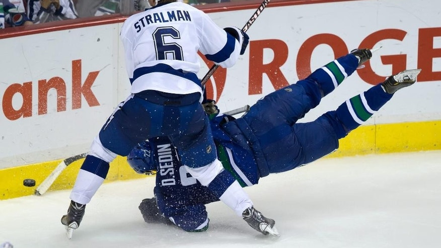 Tampa Bay Lightning's Anton Stralman (6), of Sweden, checks Vancouver Canucks' Daniel Sedin, of Sweden, during the third period of an NHL hockey game Saturday, Oct. 18, 2014, in Vancouver, British Columbia. (AP Photo/The Canadian Press, Darryl Dyck)