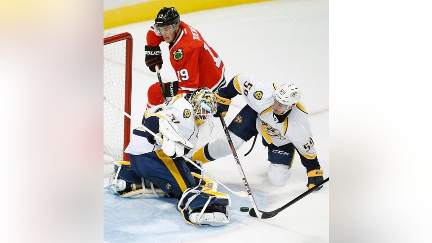 Nashville Predators defenseman Roman Josi (59) and goalie Carter Hutton (30) defend against Chicago Blackhawks center Jonathan Toews (19) during the third period of an NHL hockey game on Saturday, Oct. 18, 2014, in Chicago. (AP Photo/Andrew A. Nelles)