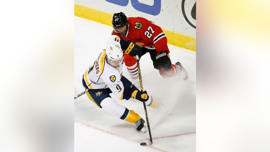 Nashville Predators center Filip Forsberg (9) and Chicago Blackhawks defenseman Johnny Oduya (27) battle during the third period of an NHL hockey game on Saturday, Oct. 18, 2014, in Chicago. (AP Photo/Andrew A. Nelles)