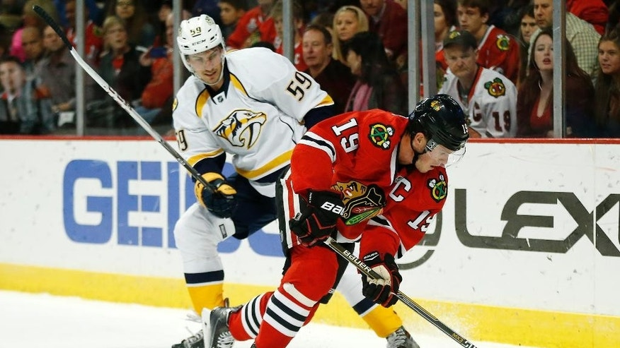 Chicago Blackhawks center Jonathan Toews (19) skates past Nashville Predators defenseman Roman Josi (59) during the second period of an NHL hockey game on Saturday, Oct. 18, 2014, in Chicago. (AP Photo/Andrew A. Nelles)