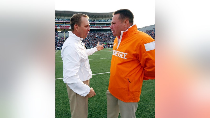 Tennessee football coach Butch Jones, left, and Mississippi football coach Hugh Freeze confer prior to their NCAA college football game in Oxford, Miss., Saturday, Oct. 18, 2014. No. 3 Mississippi won 34-3. (AP Photo/Rogelio V. Solis)