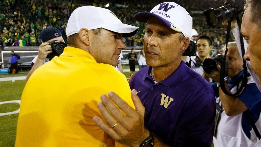 Washington coach Chris Petersen, right, greets Oregon coach Mark Helfrich after the end of an NCAA college football game in Eugene, Ore., Saturday, Oct. 18, 2014. (AP Photo/Ryan Kang)