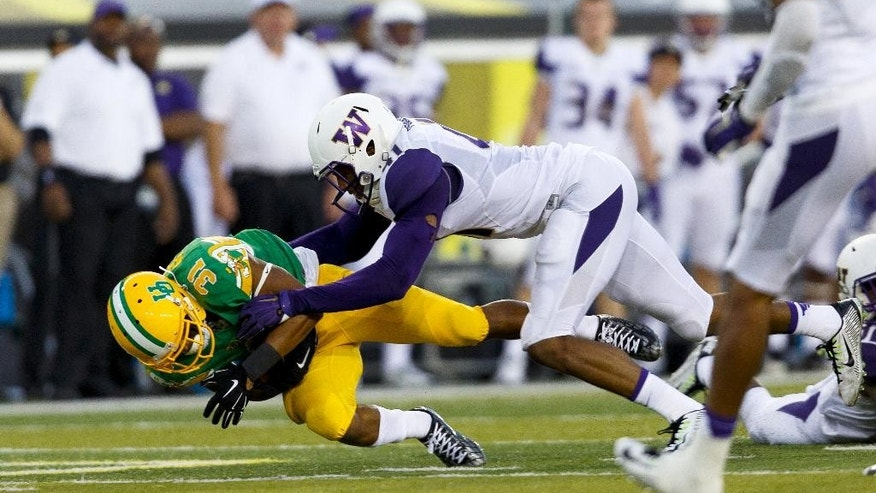 Oregon running back Kenny Bassett (31) is pushed to the ground by Washington linebacker Travis Feeney (41) during the second quarter in an NCAA college football game in Eugene, Ore., Saturday, Oct. 18, 2014. (AP Photo/Ryan Kang)