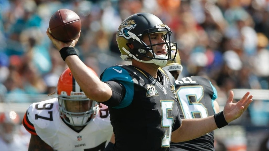 Jacksonville Jaguars quarterback Blake Bortles (5) throws a pass as Cleveland Browns outside linebacker Jabaal Sheard (97) moves in during the first half of an NFL football game in Jacksonville, Fla., Sunday, Oct. 19, 2014. (AP Photo/Stephen B. Morton)