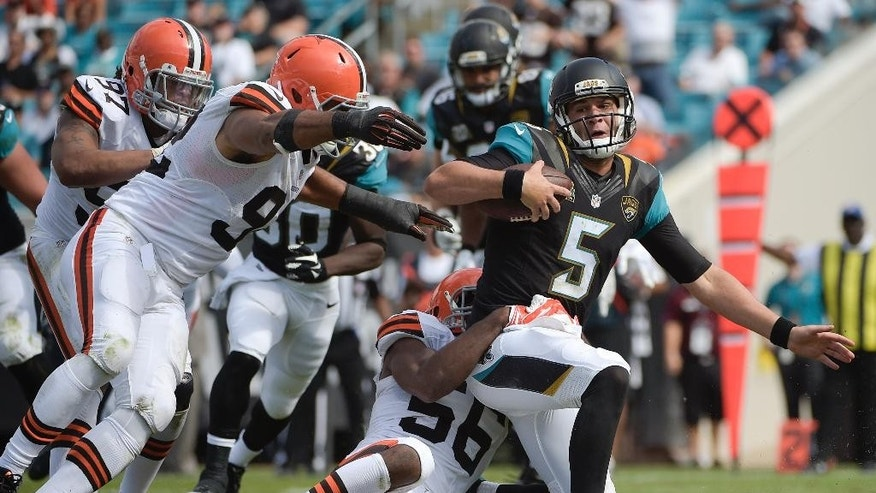 Jacksonville Jaguars quarterback Blake Bortles (5) is sacked by Cleveland Browns inside linebacker Karlos Dansby (56) during the second half of an NFL football game in Jacksonville, Fla., Sunday, Oct. 19, 2014. (AP Photo/Phelan M. Ebenhack)