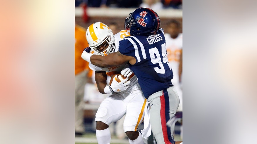 Tennessee running back Derrell Scott (24) is tackled behind the line of scrimmage by Mississippi defensive tackle Issac Gross (94) in the second half of an NCAA college football game in Oxford, Miss., Saturday, Oct. 18, 2014. No. 3 Mississippi won 34-3. (AP Photo/Rogelio V. Solis)
