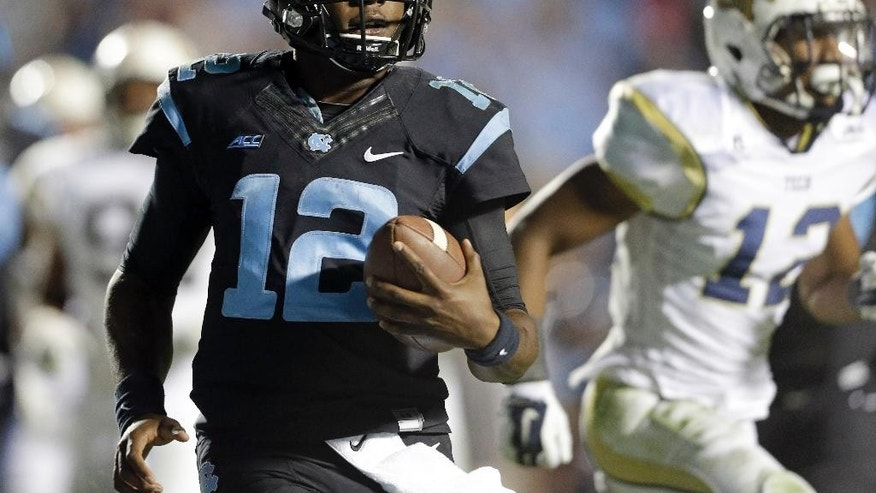 North Carolina quarterback Marquise Williams (12) runs for a touchdown against Georgia Tech during the second half of an NCAA college football game in Chapel Hill, N.C., Saturday, Oct. 18, 2014. North Carolina won 48-43. (AP Photo/Gerry Broome)