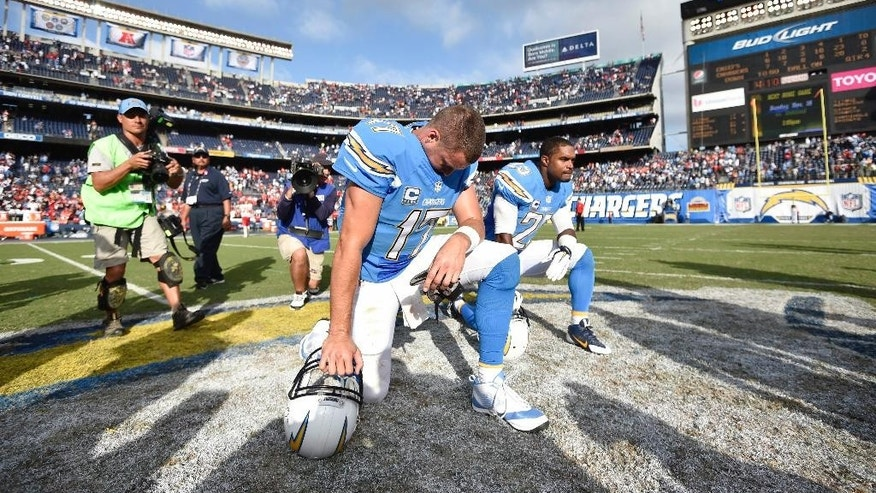 San Diego Chargers quarterback Philip Rivers (17) kneels on the field with San Diego Chargers defensive back Darrell Stuckey (25) after an NFL football game against the Kansas City Chiefs Sunday, Oct. 19, 2014, in San Diego.  (AP Photo/Denis Poroy)