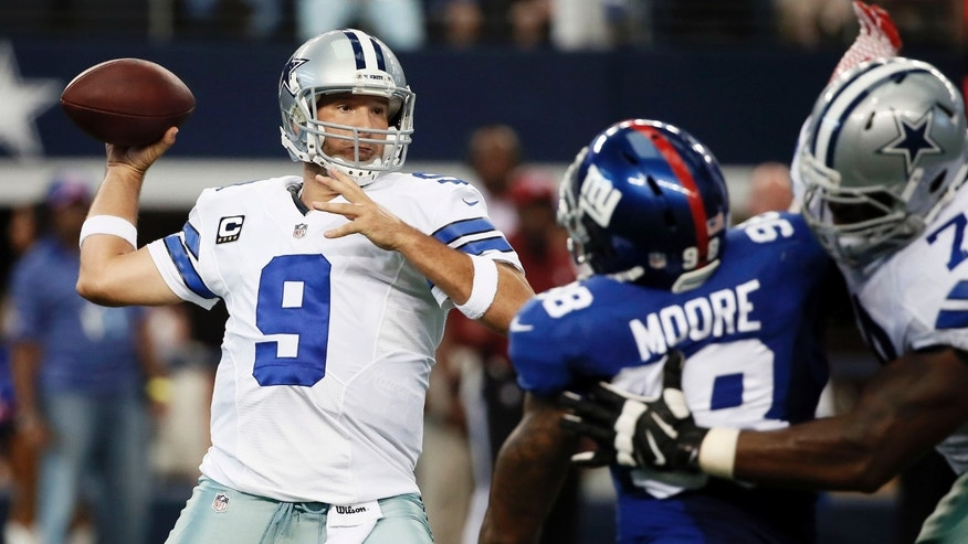 Dallas Cowboys' Tony Romo (9) prepares to pass as Jermey Parnell, right, defends against a rush by New York Giants defensive end Damontre Moore, center, during the first half of an NFL football game, Sunday, Oct. 19, 2014, in Arlington, Texas. (AP Photo/Brandon Wade)