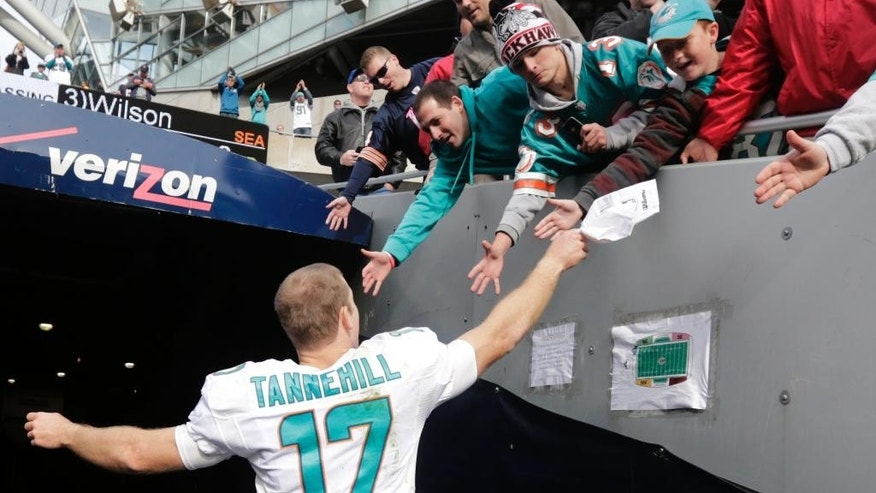 Miami Dolphins quarterback Ryan Tannehill celebrates with fans as he runs off the field after an NFL football game against the Chicago Bears Sunday, Oct. 19, 2014 in Chicago. The Dolphins won 27-14. (AP Photo/Charles Rex Arbogast)