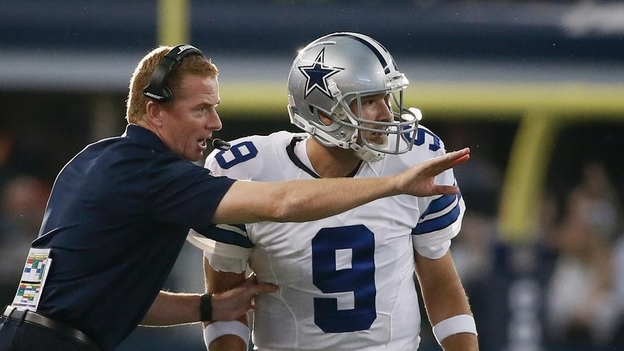 Dallas Cowboys head coach Jason Garrett instructs Tony Romo (9) during the second half of an NFL football game against the New York Giants, Sunday, Oct.  19, 2014, in Arlington, Texas. (AP Photo/Brandon Wade)