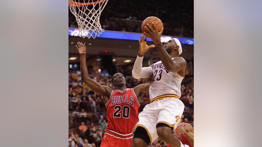 Cleveland Cavalier's LeBron James, right, shoots over Chicago Bull's Tony Snell during the first quarter of an NBA preseason basketball game Monday, Oct. 20, 2014, in Columbus, Ohio. (AP Photo/Jay LaPrete)
