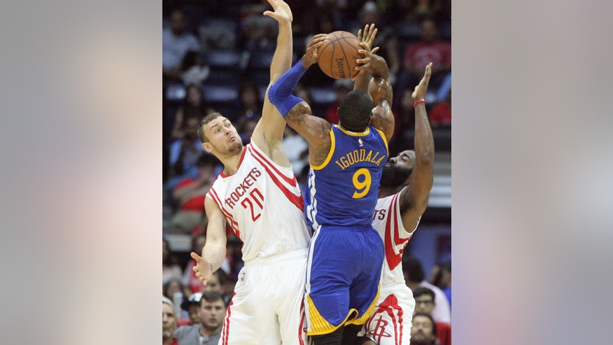 Houston Rockets Donatas Motiejunas, left, and James Harden defend Golden State Warriors Andre Iguodala, center, during an NBA preseason basketball game in Hidalgo, Texas, Sunday, Oct. 19, 2014. (AP Photo/Delcia Lopez)