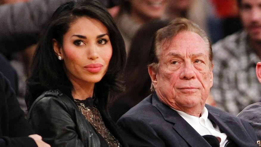 FILE - In this Dec. 19, 2010, file photo, Los Angeles Clippers owner Donald Sterling, right, and V. Stiviano, left, watch the Clippers play the Los Angeles Lakers during an NBA preseason basketball game in Los Angeles. A judge who was on the verge of allowing a defamation suit by Sterling's mistress to go forward decided to reconsider after hearing from Shelley Sterling's lawyer Friday, Oct. 17, 2014. Attorney Pierce O'Donnell called the filing by V. Stiviano an act of spite and revenge against the estranged wife of the former Los Angeles Clippers' owner. (AP Photo/Danny Moloshok, File)